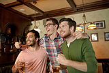 friends with beer watching sport at bar or pub