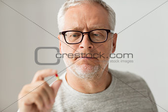 close up of senior man taking medicine pill