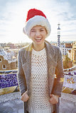 smiling trendy woman in Santa hat at Guell Park in Barcelona
