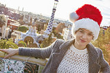 traveller woman in Santa hat at Guell Park sitting on bench
