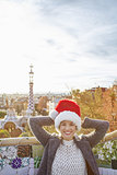traveller woman in Santa hat at Guell Park relaxing on bench