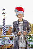 smiling tourist woman in Santa hat at Guell Park in Barcelona