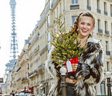 happy modern woman with Christmas tree in Paris, France