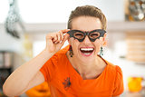 woman in party bat glasses in the Halloween decorated kitchen