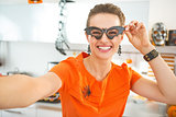 smiling woman in Halloween decorated kitchen taking selfie