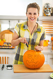 woman in kitchen carving big orange pumpkin Jack-O-Lantern