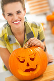 woman with a big orange pumpkin Jack-O-Lantern in kitchen