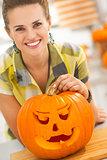 woman with a big orange pumpkin Jack-O-Lantern in kitchen