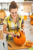 happy woman prepare big orange pumpkin for Halloween party