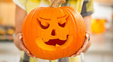 Closeup on housewife showing big pumpkin Jack-O-Lantern