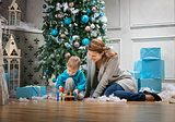 Preschool boy and his mom playing with wooden hammer toy while sitting beside Christmas tree