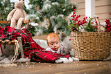 Cute baby boy lying on floor among Christmas decorations at home