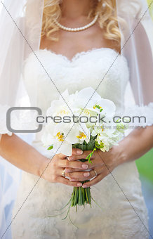 Cropped view of elegant bride holding flowers