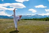 Man in white kimono and black belt training karate on mountain background.