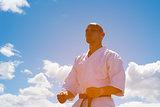 Man in kimono meditating on sky background.