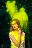Beautiful young woman covered yellow dry paint holi
