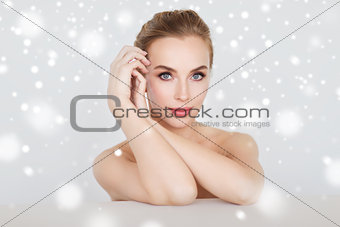 beautiful young woman face and hands over snow