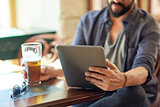 close up of man with tablet pc and beer at pub