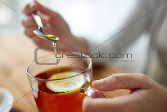 close up of woman adding honey to tea with lemon