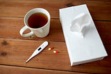 cup of tea, paper wipes and thermometer with pills