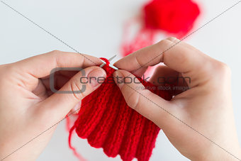 close up of hands knitting with needles and yarn