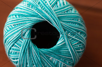 close up of turquoise knitting yarn ball on wood