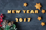 background with baked gingerbread words new year 2017 and star-shaped biscuits with decorated fir branch. creative idea