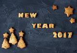 background with baked gingerbread words new year 2017 with star-shaped and christmas tree - shaped biscuits. creative idea