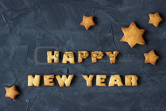 background with baked gingerbread stars and words happy new year. creative idea