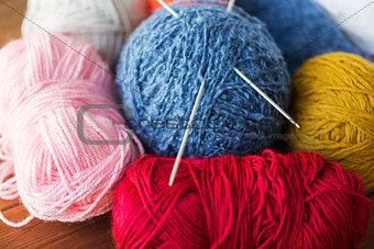 knitting needles and balls of yarn on wood