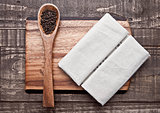 Pepper on spoon and kitchen towel on wooden board