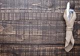 Knife and fork inside kitchen towel on wooden board