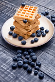 Blueberries and sweet waffles on plate and blue wood