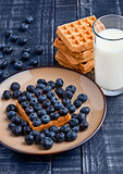 Blueberries and waffles on plate with milk glass