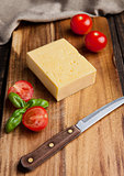 Cheese with tomatoes and basil on wood with knife
