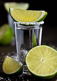 Tequila silver shot with lime slices and salt on wooden board