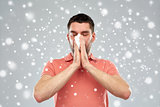 sick man with paper wipe blowing nose over snow