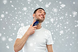 smiling man shaving beard with trimmer over snow