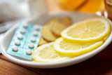 lemon slices, pills and ginger on plate
