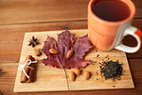 cup of tea, maple leaf and almond on wooden board