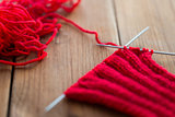 hand-knitted item with knitting needles on wood