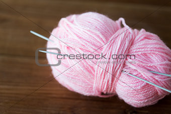 knitting needles and ball of pink yarn on wood