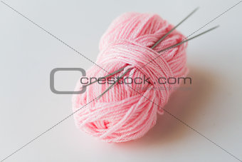 knitting needles and ball of pink yarn