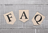 FAQ paper letter symbol motivation on wooden board