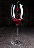 Pouring red wine from bottle to the glass on wood