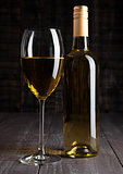 Bottle and glass of white wine on wooden board