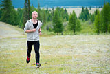 Man running on grass field at mountain background