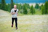 Man running on grass field at mountain background