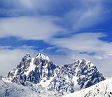 Mounts Ushba and Chatyn and blue sky with clouds in winter wind