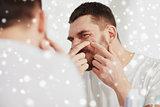 man squeezing pimple at bathroom mirror